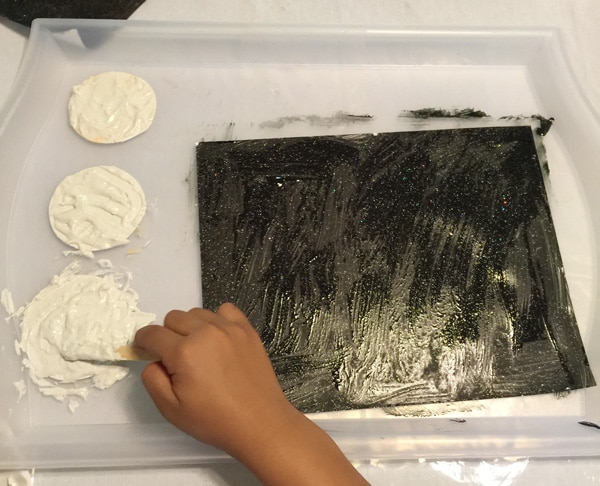 Creating a realistic looking moon with the kids by adding flour to white paint