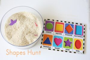 Toddler learning shapes through sensory bin rice hunt