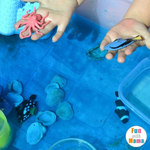 under the sea sensory bin examining the fish (Small)