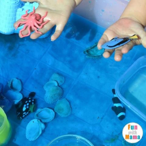 under the sea sensory bin examining the fish (Small)